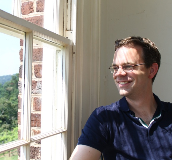 Jelte Olthof headshot - a white man smiling and looking out a window