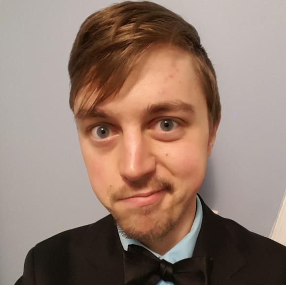 Jason Michálek headshot - a young white man in a bowtie